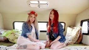 Pares de las mujeres jovenes vestidas en los estilos del indie y de Boho que se sientan en remolque auto almacen de video