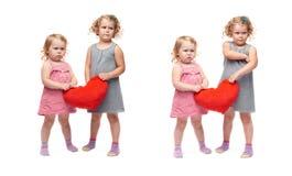 Pares de las niñas jovenes que se colocan sobre fondo blanco aislado Fotos de archivo libres de regalías