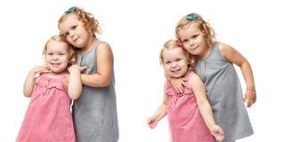 Pares de las niñas jovenes que se colocan sobre fondo blanco aislado Fotografía de archivo