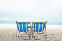 Pares de las sillas de playa de nylon coloridas con el mar agradable del paraíso y la arena blanca Fotografía de archivo libre de regalías