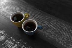 Pares de las tazas de café coloridas sobre una tabla blanco y negro fotografía de archivo libre de regalías