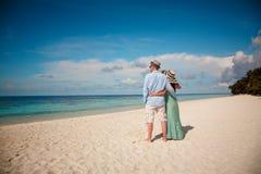 Pares de las vacaciones que caminan en la playa tropical Maldivas Fotografía de archivo