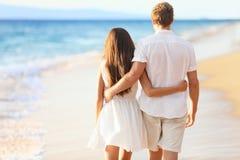 Pares de las vacaciones que recorren en la playa Fotos de archivo libres de regalías