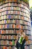Pares de los adolescentes femeninos que toman el selfie delante de la torre enorme del estante en feria de libro internacional imagenes de archivo