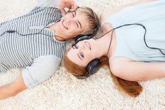 Pares de los adolescentes que escuchan la música Imágenes de archivo libres de regalías