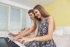 Pares de los adolescentes que juegan en el piano electrónico Fotografía de archivo