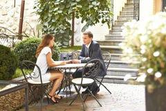 Pares de los amantes que cenan en hombre hermoso del restaurante en mujer hermosa del traje de negocios elegante en la sentada de Imagen de archivo