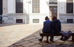 Pares de los amantes que se sientan en un banco Foto de archivo