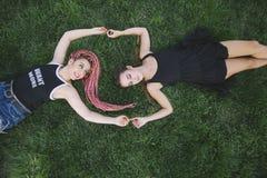 Pares de los amigos adolescentes que llevan a cabo las manos en la hierba Fotos de archivo libres de regalías