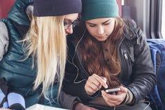 Pares de los amigos femeninos que miran el smartphone mientras que en el tren Foto de archivo libre de regalías