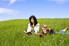 Pares de los amigos que gozan de un libro Imagen de archivo libre de regalías