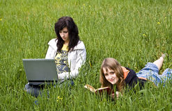 Pares de los amigos que gozan en el prado Foto de archivo libre de regalías