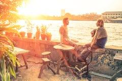 Pares de los amigos que hablan en la puesta del sol Imagen de archivo libre de regalías