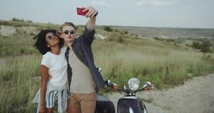 Pares de los amigos que tienen una grieta de una época, tomando las fotos de la diversión así como la moto siempre estética almacen de metraje de vídeo