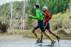Pares de los atletas de sexo masculino jovenes que corren abajo del camino Fotografía de archivo