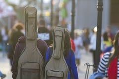 Pares de los buskers jovenes con las guitarras en su parte posterior que caminan abajo de la calle Fotos de archivo libres de regalías