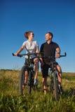 Pares de los ciclistas que montan las bicicletas en prado Fotografía de archivo