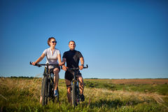 Pares de los ciclistas que montan las bicicletas en prado Imagen de archivo