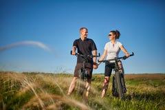 Pares de los ciclistas que montan las bicicletas en prado Imagenes de archivo