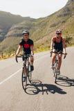 Pares de los ciclistas que montan las bicicletas en una carretera nacional Foto de archivo