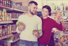 Pares de los clientes que compran comida enlatada Foto de archivo libre de regalías
