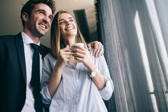 Pares de los colegas felices que hablan mientras que se coloca en la ventana de la oficina con las tazas de café imágenes de archivo libres de regalías