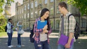 Pares de los compañeros de clase que comunican en patio de la universidad durante rotura, amigos almacen de metraje de vídeo