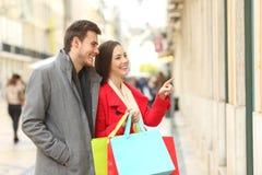Pares de los compradores que hacen compras en la calle Imagen de archivo libre de regalías