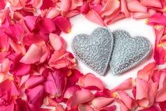 Pares de los corazones tallados decorativos rodeados por los pétalos color de rosa rojos imagenes de archivo