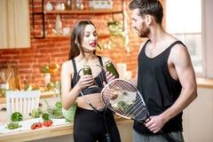 Pares de los deportes que comen la comida sana en la cocina en casa imagen de archivo