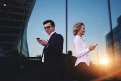 Pares de los empresarios jovenes que usan los teléfonos móviles que se oponen al edificio de oficinas con la reflexión del paisaj Fotografía de archivo libre de regalías