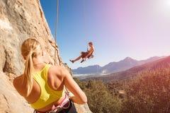 Pares de los escaladores de roca en cuerda del belay foto de archivo