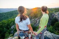 Pares de los escaladores que descansan y que disfrutan de la opinión hermosa de la naturaleza Foto de archivo libre de regalías