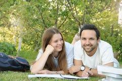 Pares de los estudiantes jovenes que estudian en el parque Imagenes de archivo