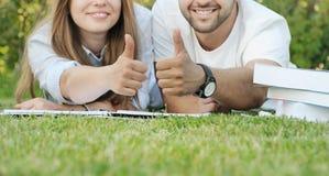 Pares de los estudiantes jovenes studing en el parque Fotografía de archivo libre de regalías