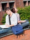 Pares de los estudiantes que usan la computadora portátil y el libro de lectura Imagen de archivo