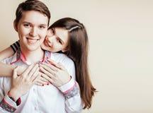 Pares de los estudiantes sonrientes felices de los adolescentes, de los colores calientes que tienen un beso, del concepto de la  Foto de archivo libre de regalías