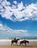 Pares de los jinetes del caballo en la playa Imágenes de archivo libres de regalías