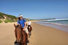 Pares de los jinetes del caballo en la playa imagenes de archivo