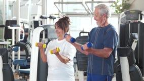 Pares de los mayores que entrenan con pesas de gimnasia almacen de video