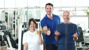 Pares de los mayores que levantan pesas de gimnasia en el gimnasio metrajes