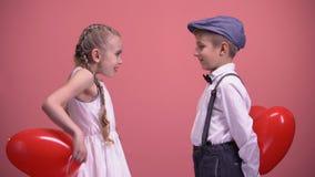 Pares de los niños lindos que intercambian los globos en forma de corazón rojos, regalo de día de San Valentín almacen de metraje de vídeo
