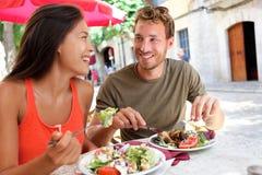 Pares de los turistas del restaurante que comen en el café al aire libre