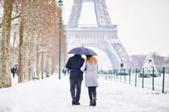 Pares de los turistas que caminan en París en un día con nevadas fuertes foto de archivo libre de regalías