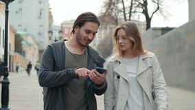 Pares de los turistas que caminan en una calle de la ciudad con usos de la navegación del uso del teléfono, el hombre y el paseo  almacen de metraje de vídeo
