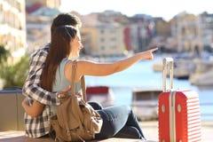 Pares de los turistas que señalan el destino de las vacaciones Imagen de archivo libre de regalías