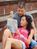 Pares de los turistas que se sientan en pasos, leyendo el mapa. Imagen de archivo