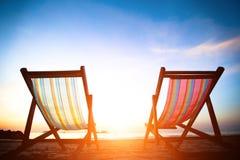 Pares de loungers da praia no mar abandonado da costa no nascer do sol Fotos de Stock Royalty Free
