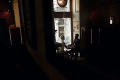 Pares de lujo de la boda que llevan a cabo las manos y que se sientan en café en morni Foto de archivo