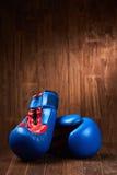 Pares de luvas de encaixotamento azuis e vermelhas na superfície de madeira contra o fundo de madeira Fotos de Stock Royalty Free
